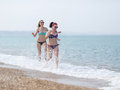 Two girls in bikini running along seashore splashing sea water Royalty Free Stock Photo