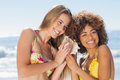 Two girls in bikinis listening to conch shell on beach Royalty Free Stock Image