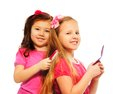 Two girls brushing hair caucasian and asian playing to be big like older sisters each other isolated on white full length portrait Stock Photo