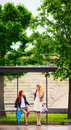 Two Girls at Bus Stop Royalty Free Stock Photography