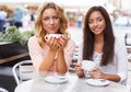 Two girls in a cafe beautiful with cups chatting summer Stock Photo