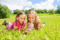Two girls caught butterfly in the jar little lay grass looking at red glass Stock Images