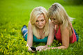 Two girls with a cell phone lying on the grass Stock Images