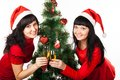 Two girls with champagne near Christmas tree Stock Photos