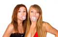 Two  girls with chewing gum bubbles Royalty Free Stock Photo