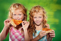 Two girls eating pizza Stock Photos