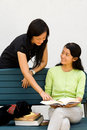 Two girls enjoy discussing a book Stock Photo