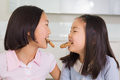 Two girls enjoying cookies in the kitchen cheerful young Royalty Free Stock Photography