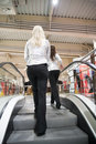 Two girls on escalators Stock Photography