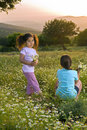 Two girls flowers field at sunset Stock Photo