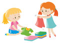 Two girls folding clothes