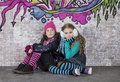 Two girls in front of the wall covered with graffiti sitting brick Royalty Free Stock Images