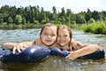 Two girls girlfriends on summer lake swimming in the lake and sm floating inflatable cushions smiling Royalty Free Stock Image