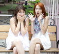 Two girls gossiping on bench at garden. Royalty Free Stock Photography