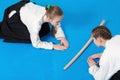 Two girls in hakama bow on aikido training black Stock Image