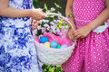Two girls hands holding an easter basket close up a of little a with eggs and flowers in the spring season during a family day Stock Photos