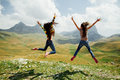Two girls happy jump in mountains with exciting view Royalty Free Stock Photo