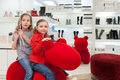Two girls having fun in a big red toy at the store childrens shoes Stock Photos