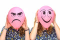 Two girls holding pink balloons with facial expressions Royalty Free Stock Photo