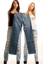 Two girls holding up a pair of jeans Stock Photos