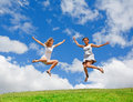 Two girls jumping Stock Image