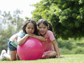 Two girls kneeling beside pink space hopper on grass in park smiling portrait Royalty Free Stock Photography