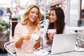 Two girls with laptop beautiful cups and in summer cafe Stock Photo
