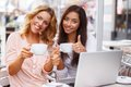 Two girls with laptop beautiful cups and in summer cafe Royalty Free Stock Images