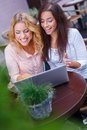 Two girls with laptop beautiful in summer cafe Royalty Free Stock Images