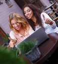 Two girls with laptop beautiful in summer cafe Royalty Free Stock Photo