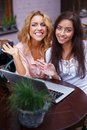 Two girls with laptop beautiful in summer cafe Stock Images