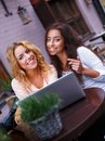 Two girls with laptop beautiful in summer cafe Stock Photography