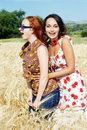 Two girls laughing in wheat field Royalty Free Stock Images
