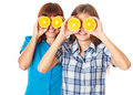 Two girls are looking through oranges Royalty Free Stock Photo