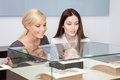 Two girls looking at showcase with jewelry jeweler s shop concept of wealth and luxurious life Stock Image