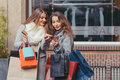 Two girls looking at smart phone in front of showwindow with sal Royalty Free Stock Photo