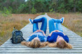 Two girls lying on their backs on wooden path in nature Royalty Free Stock Photo