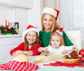Two girls with mother baking christmas cookies in the kitchen adorable Stock Photos