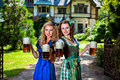 Two girls with oktoberfest beer stein in dirndl dress holding Stock Photo