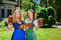 Two girls with oktoberfest beer stein and pretzel in dirndl dress holding Royalty Free Stock Image