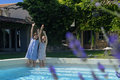 Two girls paddling on pool young in their dresses standing in the swimming of a family home in provence france arms raised Royalty Free Stock Image