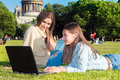 Two girls in the park with a laptop friends tablet computer sitting on grass summer youth lifestyle Royalty Free Stock Photography