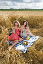 Two girls on picnic in wheat field Stock Photos