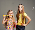 Two girls play bubble on a gray background Royalty Free Stock Photography