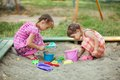 Two girls play in the sandbox at playground Royalty Free Stock Images