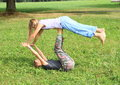 Two girls playing and exercising yoga on meadow