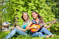 Two girls playing guitar and flute in the park on summer day Stock Image
