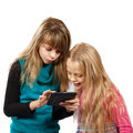 Two girls playing with tablet pc looking at something in on a white background Stock Photo