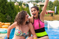 Two girls at the pool in a fun park having a god time. Royalty Free Stock Photo