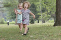 Two girls race down a hill in a park Stock Images